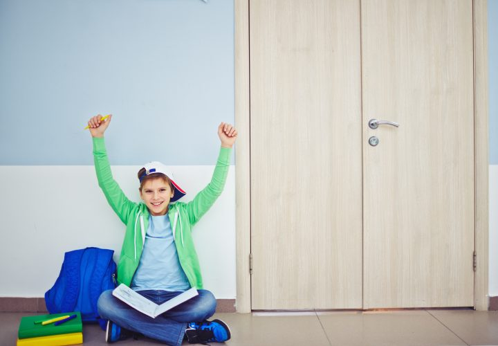 Ecstatic schoolboy with book and raised arms sitting on the floor by classroom door